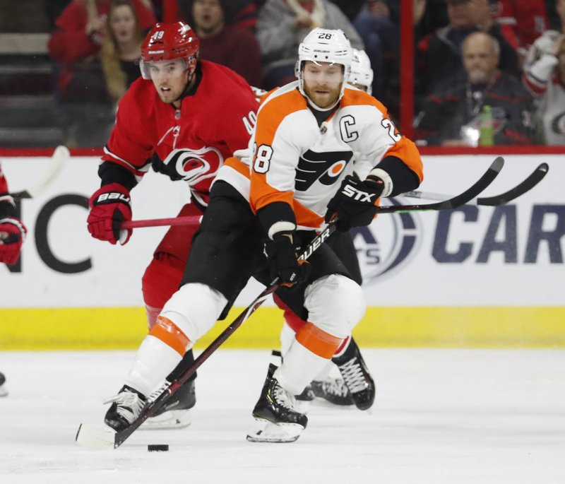 Philadelphia Flyers' Claude Giroux (28) moves the puck after taking it from Carolina Hurricanes' Victor Rask (49) during the first period of an NHL hockey game, Monday, Dec. (AP Photo/Karl B DeBlaker)