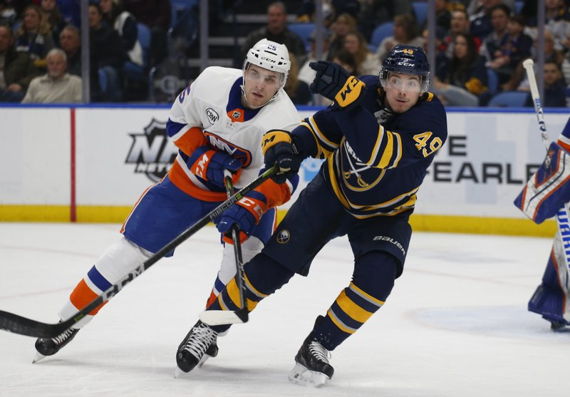 Buffalo Sabres forward C.J. Smith (49) and New York Islanders defenseman Devon Toews (25) battle for position during the first period of an NHL hockey game, Monday, Dec. (AP Photo/Jeffrey T. Barnes)