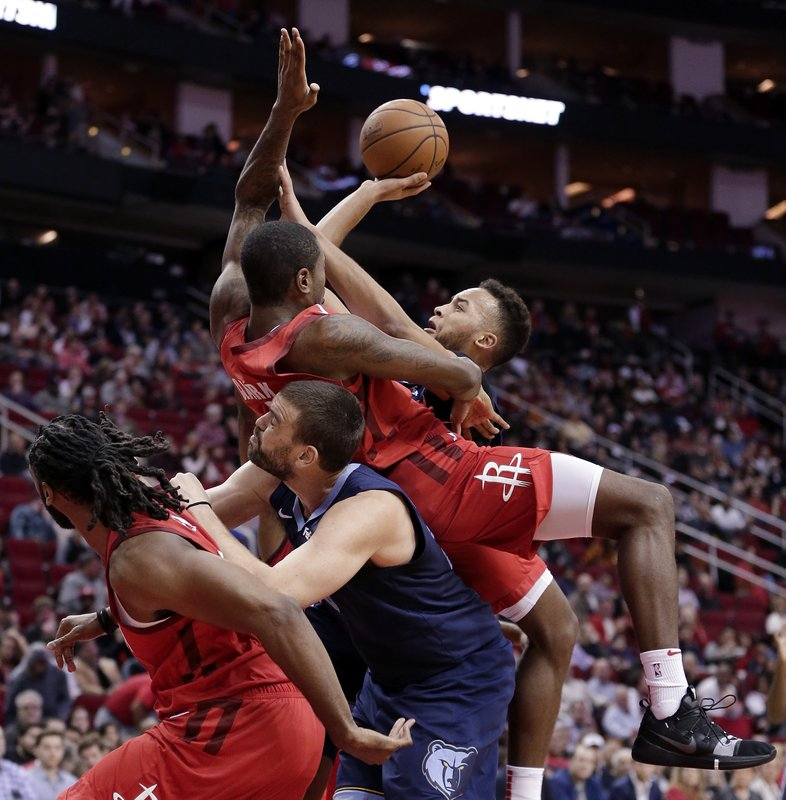 Memphis Grizzlies forward Kyle Anderson, right, shoots as Houston Rockets forward Gary Clark, top, falls onto center Marc Gasol, who pushes off of Houston Rockets center Nene, left, during the first half of an NBA basketball game Monday, Dec. (AP Photo/Michael Wyke)