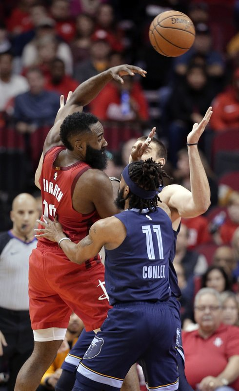Houston Rockets guard James Harden (13) passes the ball over Memphis Grizzlies guard Mike Conley (11) and center Marc Gasol, back, during the first half of an NBA basketball game Monday, Dec. (AP Photo/Michael Wyke)