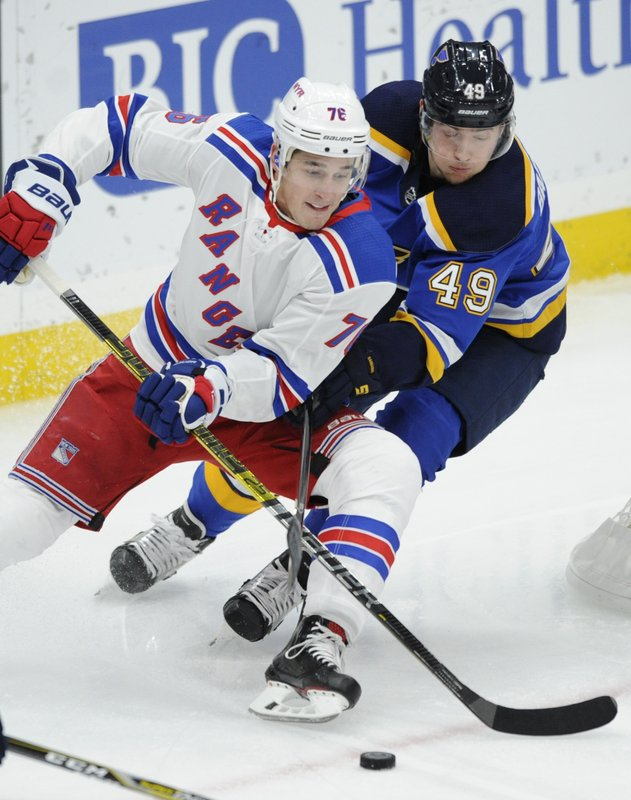 St. Louis Blues' Ivan Barbashev (49), of Russia, reaches for the puck with New York Rangers' Brady Skjei (76) defending during the first period of an NHL hockey game Monday, Dec. (AP Photo/Bill Boyce)