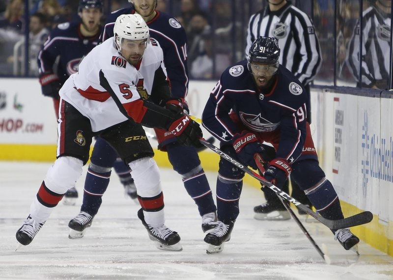 Ottawa Senators' Cody Ceci, left, and Columbus Blue Jackets' Anthony Duclair chase the puck during the second period of an NHL hockey game Monday, Dec. (AP Photo/Jay LaPrete)