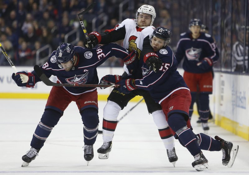 Ottawa Senators' Chris Tierney, center, tries to skate between Columbus Blue Jackets' Boone Jenner, left, and Markus Nutivaara, of Finland, during the first period of an NHL hockey game Monday, Dec. (AP Photo/Jay LaPrete)