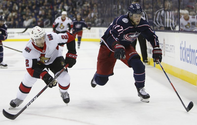 Ottawa Senators' Dylan DeMelo, left, and Columbus Blue Jackets' Josh Anderson chase the puck during the second period of an NHL hockey game Monday, Dec. (AP Photo/Jay LaPrete)