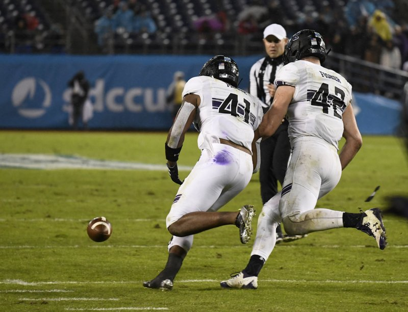 Northwestern safety Jared McGee (41) picks up a fumble next to linebacker Paddy Fisher (42) during the second half of the Holiday Bowl NCAA college football game against Utah Monday, Dec. (AP Photo/Denis Poroy)