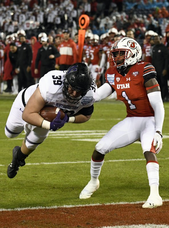 Northwestern offensive lineman Trey Klock (39) dives past Utah defensive back Jaylon Johnson (1) for a touchdown during the second half of the Holiday Bowl NCAA college football game against Utah, Monday, Dec. (AP Photo/Denis Poroy)