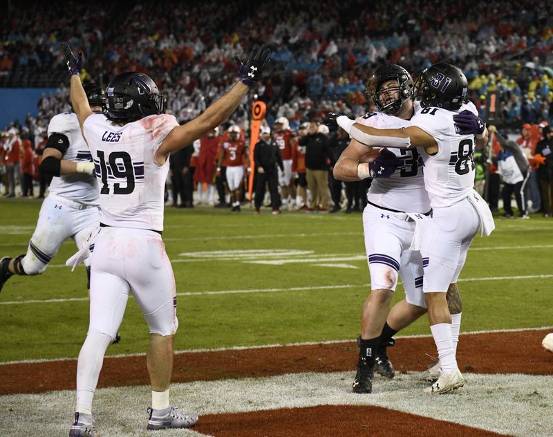 Northwestern offensive lineman Trey Klock (39), center, is congratulated by wide receiver Ramaud Chiaokhiao-Bowman (81) after scoring a touchdown during the second half of the Holiday Bowl NCAA college football game against Utah, Monday, Dec. (AP Photo/Denis Poroy)