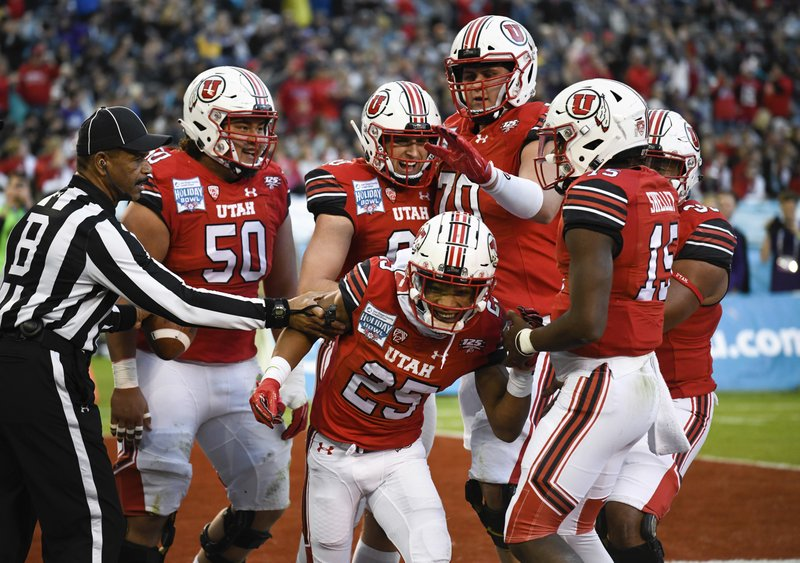Utah players congratulate wide receiver Jaylen Dixon (25) after scoring a touchdown during the first half of the Holiday Bowl NCAA college football game against Northwestern, Monday, Dec. (AP Photo/Denis Poroy)