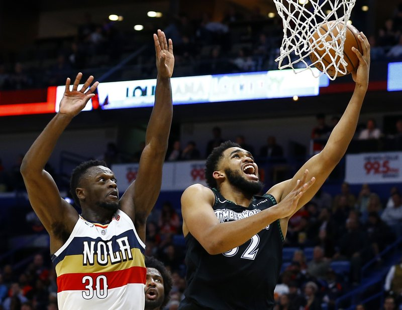 Minnesota Timberwolves center Karl-Anthony Towns (32) makes a basket as New Orleans Pelicans forward Julius Randle (30) tries to defend during the first half of an NBA basketball game, Monday, Dec. (AP Photo/Butch Dill)