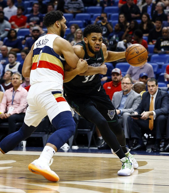 Minnesota Timberwolves center Karl-Anthony Towns (32) is fouled by New Orleans Pelicans center Jahlil Okafor (8) as he drives to the basket during the first half of an NBA basketball game, Monday, Dec. (AP Photo/Butch Dill)