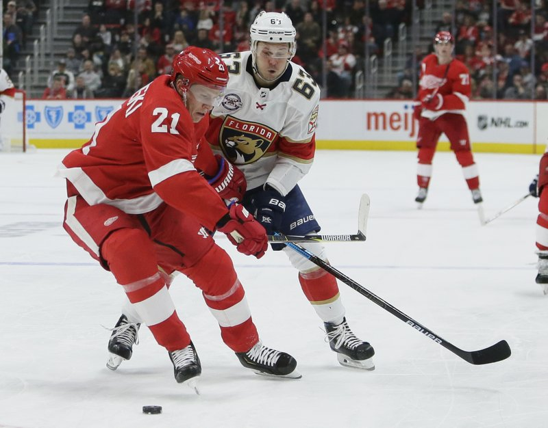 Detroit Red Wings defenseman Dennis Cholowski (21) tries to keep Florida Panthers right wing Evgenii Dadonov (63), of Russia, from getting to the puck during the third period of an NHL hockey game Monday, Dec. (AP Photo/Duane Burleson)