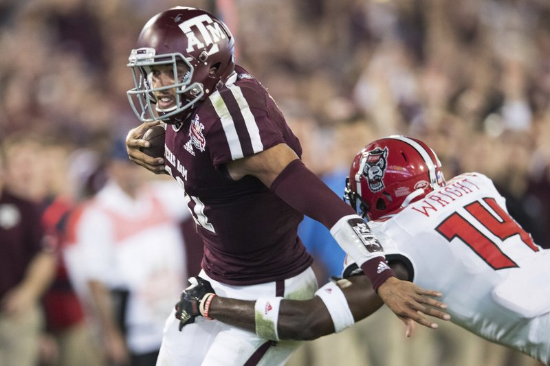 Texas A&M quarterback Kellen Mond (11) is tackled by North Carolina State safety Dexter Wright (14) during the first half of the Gator Bowl NCAA college football game Monday, Dec. (James Gilbert/The Florida Times-Union via AP)