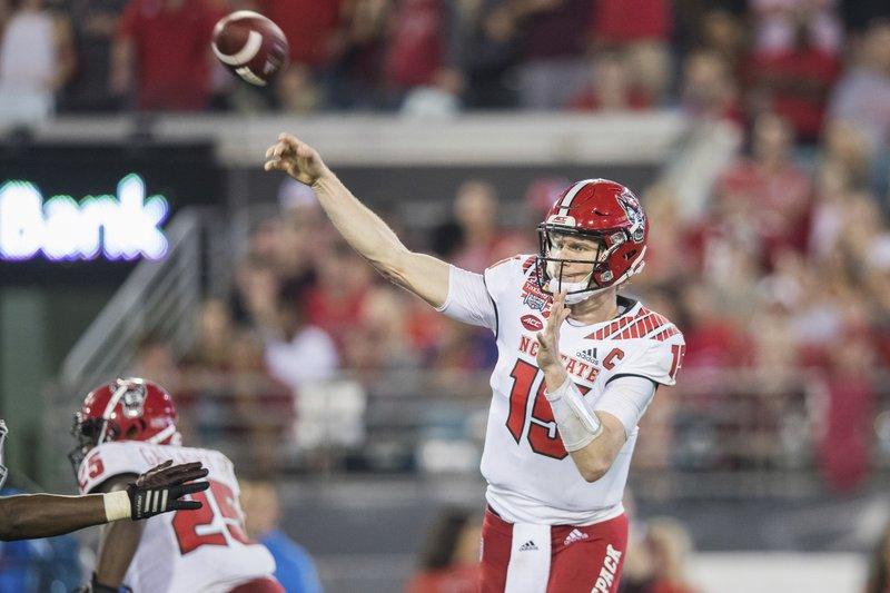 North Carolina State quarterback Ryan Finley (15) throws a pass against Texas A&M during the first half of the Gator Bowl NCAA college football game Monday, Dec. (James Gilbert/The Florida Times-Union via AP)