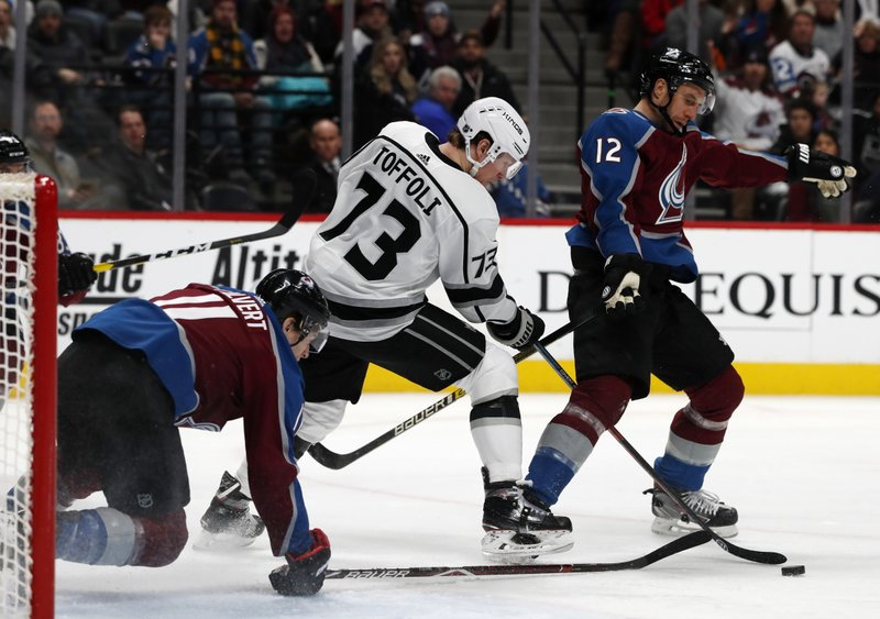 Los Angeles Kings right wing Tyler Toffoli, center, battles for control of the puck with Colorado Avalanche left wing Matt Calvert, left, and defenseman Patrik Nemeth during the second period of an NHL hockey game Monday, Dec. (AP Photo/David Zalubowski)