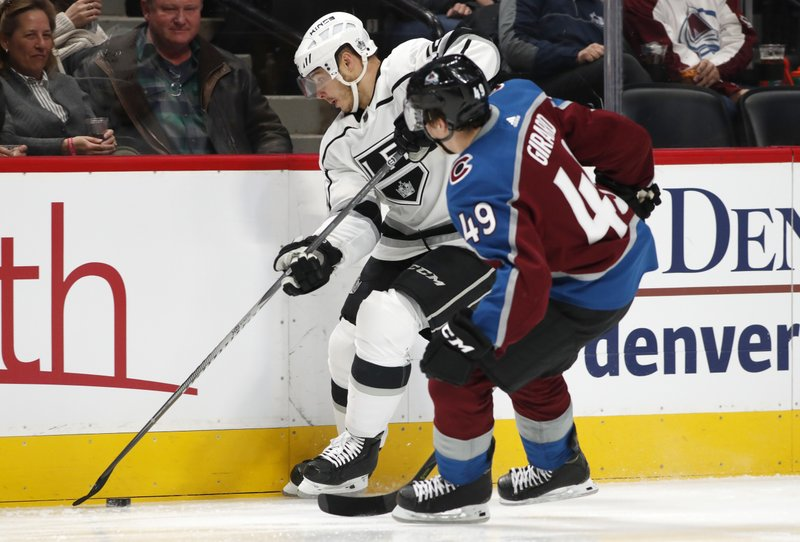 Los Angeles Kings right wing Dustin Brown, back, collects the puck along the boards as Colorado Avalanche defenseman Samuel Girard defends during the second period of an NHL hockey game Monday, Dec. (AP Photo/David Zalubowski)