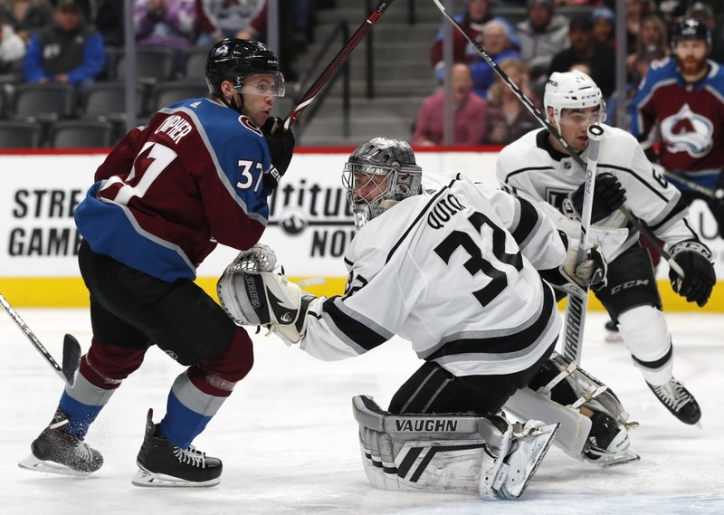 Colorado Avalanche left wing J.T. Compher watches the puck as Los Angeles Kings goaltender Jonathan Quick tries to make a glove save of a shot as defenseman Jake Muzzin defends during the first period of an NHL hockey game Monday, Dec. (AP Photo/David Zalubowski)