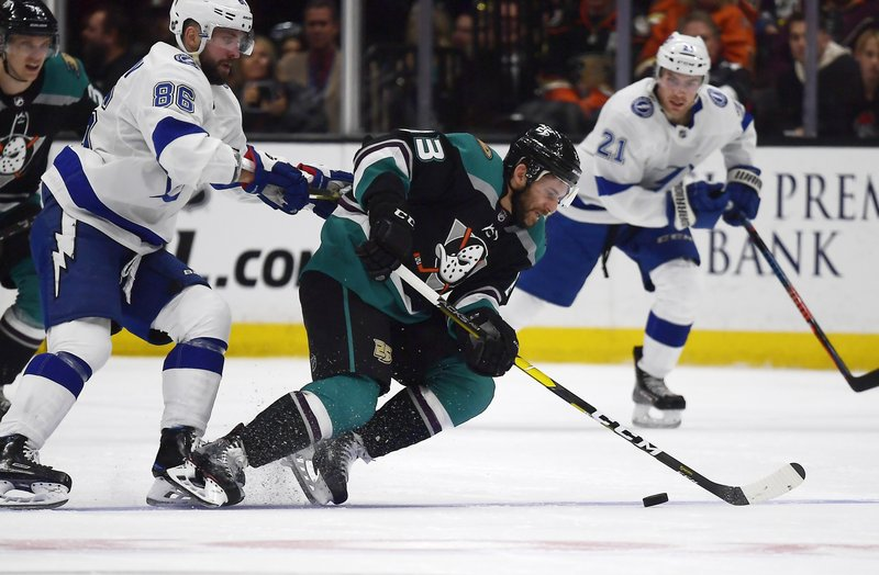 Anaheim Ducks center Brian Gibbons, center, falls as he takes the puck while under pressure from Tampa Bay Lightning right wing Nikita Kucherov, left, as center Brayden Point watches during the second period of an NHL hockey game Monday, Dec. (AP Photo/Mark J. Terrill)