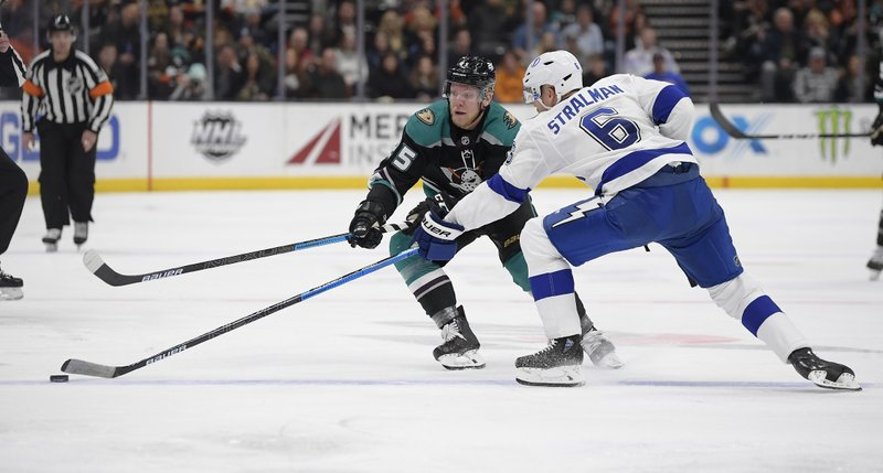 Anaheim Ducks right wing Ondrej Kase, left, and Tampa Bay Lightning defenseman Anton Stralman reach for the puck during the second period of an NHL hockey game Monday, Dec. (AP Photo/Mark J. Terrill)