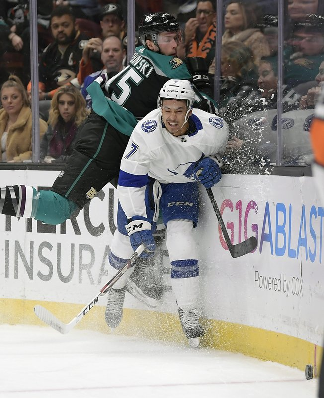 Anaheim Ducks defenseman Andy Welinski, left, and Tampa Bay Lightning right wing Mathieu Joseph battle for the puck during the first period of an NHL hockey game Monday, Dec. (AP Photo/Mark J. Terrill)