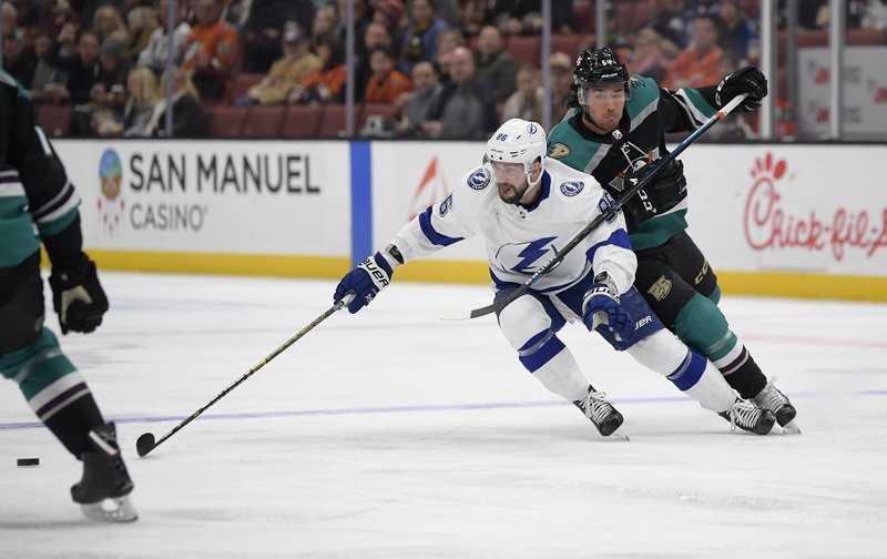 Tampa Bay Lightning right wing Nikita Kucherov, left, reaches for the puck as Anaheim Ducks right wing Kiefer Sherwood defends during the first period of an NHL hockey game Monday, Dec. (AP Photo/Mark J. Terrill)