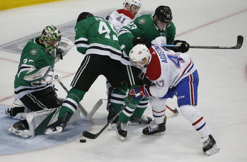 Dallas Stars goaltender Ben Bishop (30) defends as Montreal Canadiens left wing Kenny Agostino (47) tries to get the puck past Stars defenders Roman Polak (45) and Esa Lindell (23) during the second period of an NHL hockey game in Dallas, Monday, Dec. (AP Photo/Michael Ainsworth)