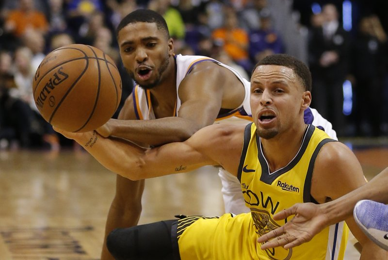 Golden State Warriors guard Stephen Curry, right, and Phoenix Suns forward Mikal Bridges vie for the ball during the first half of an NBA basketball game Monday, Dec. (AP Photo/Rick Scuteri)