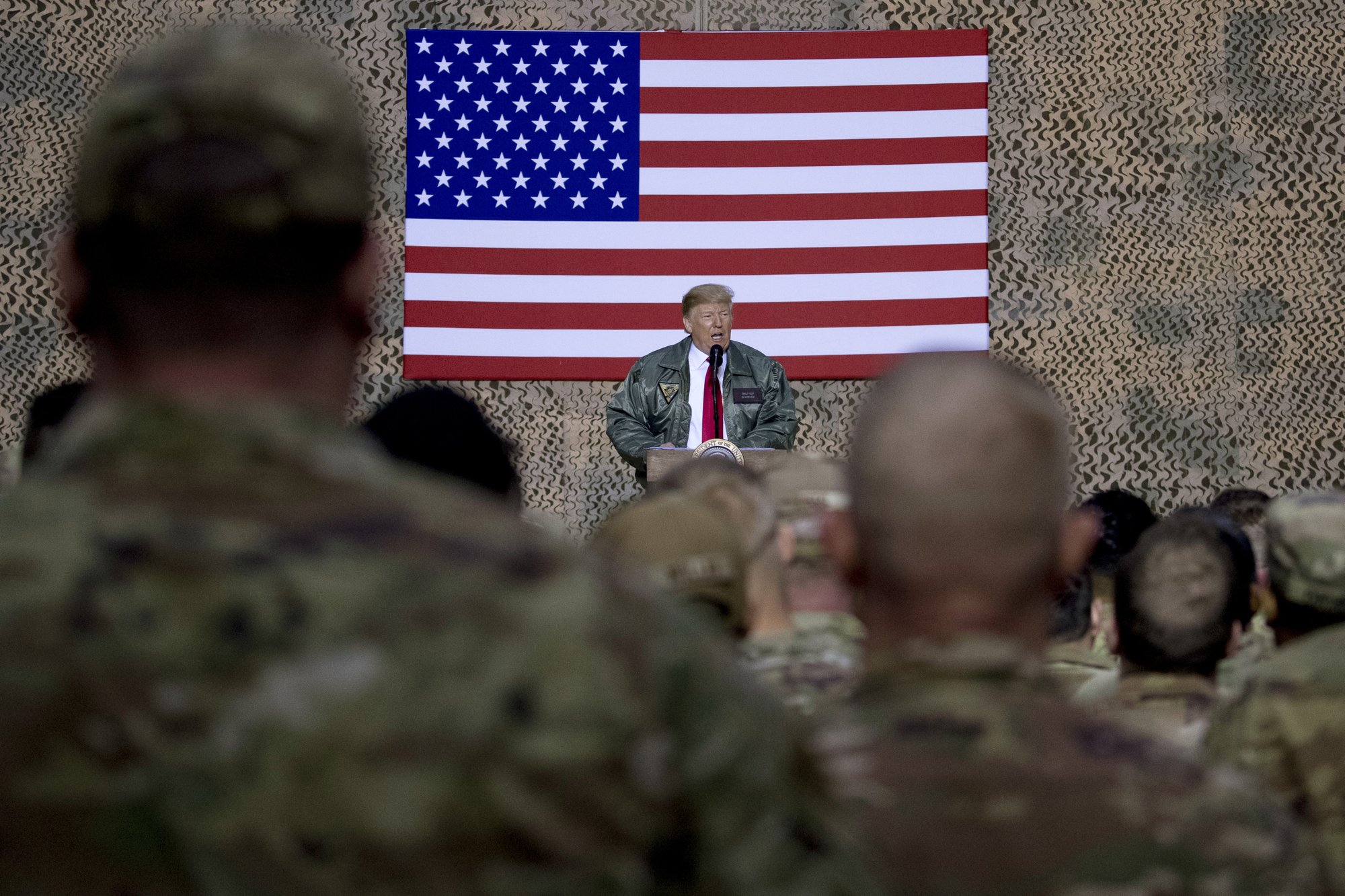 President Donald Trump speaks at a hanger rally at Al Asad Air Base, Iraq, Wednesday, Dec. 26, 2018. In a surprise trip to Iraq, President Donald Trump on Wednesday defended his decision to withdraw U.S. forces from Syria where they have been helping battle Islamic State militants. (AP Photo/Andrew Harnik)