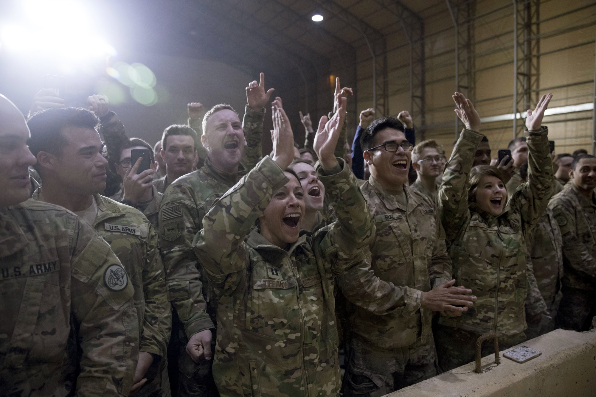 Members of the military cheer as President Donald Trump speaks at a hanger rally at Al Asad Air Base, Iraq, Wednesday, Dec. 26, 2018. President Donald Trump, who is visiting Iraq, says he has 'no plans at all' to remove US troops from the country. (AP Photo/Andrew Harnik)