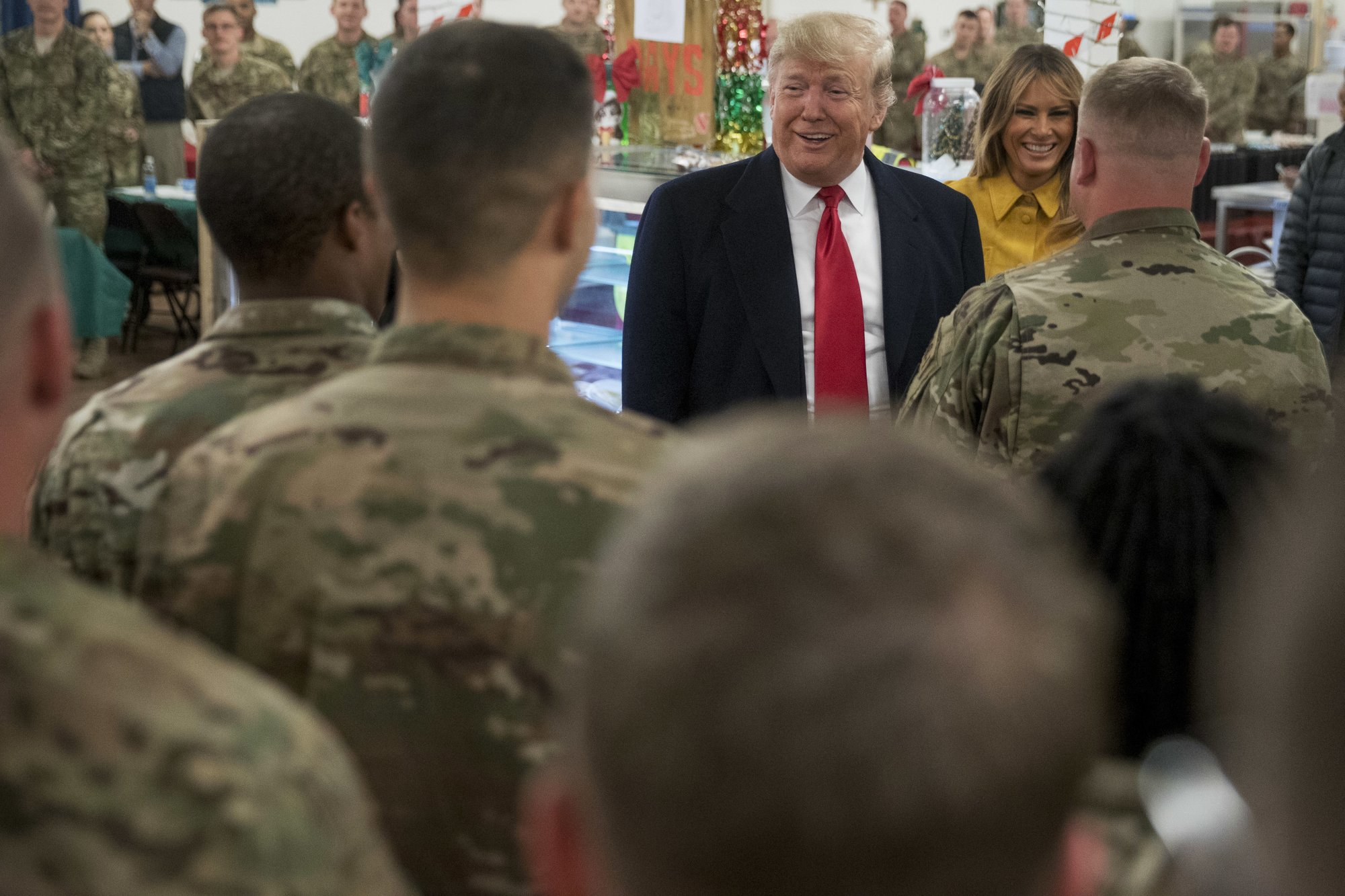 President Donald Trump and first lady Melania Trump visit with members of the military at a dining hall at Al Asad Air Base, Iraq, Wednesday, Dec. 26, 2018. (AP Photo/Andrew Harnik)