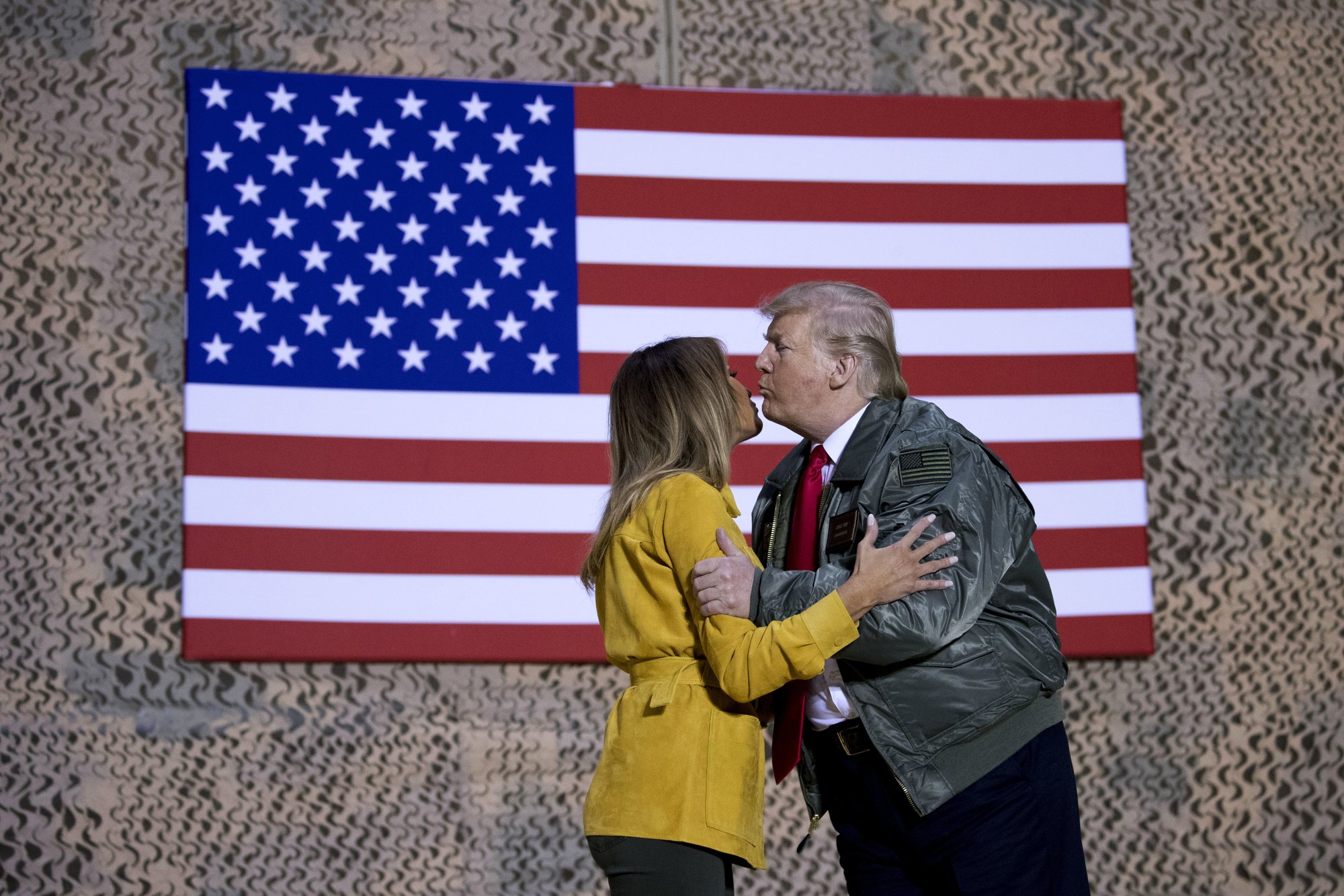 President Donald Trump kisses first lady Melania Trump during a hanger rally at Al Asad Air Base, Iraq, Wednesday, Dec. 26, 2018. President Donald Trump, who is visiting Iraq, says he has 'no plans at all' to remove U.S. troops from the country. (AP Photo/Andrew Harnik)
