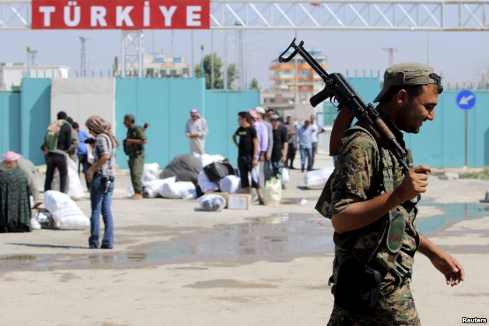 A Kurdish People's Protection Units (YPG) fighter walks near residents wh