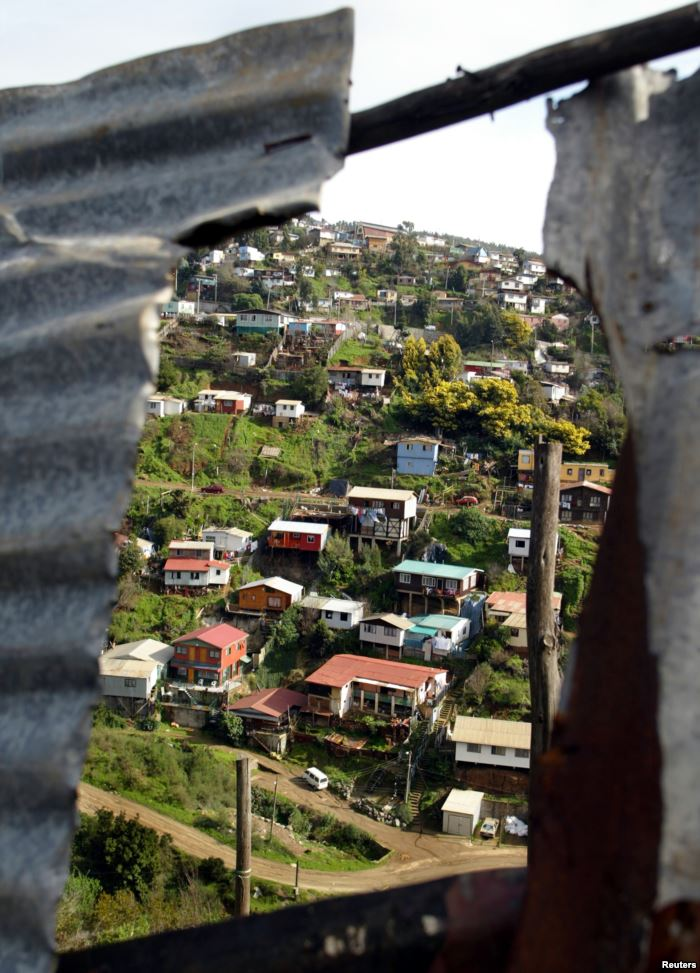A low-income neighborhood is seen through the roof of a shanty on a hillside