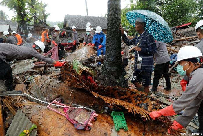 A man holding an umbrella watches as personnel search through the debris of h