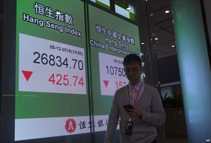 A man walks past an electronic board showing Hong Kong share index outside a