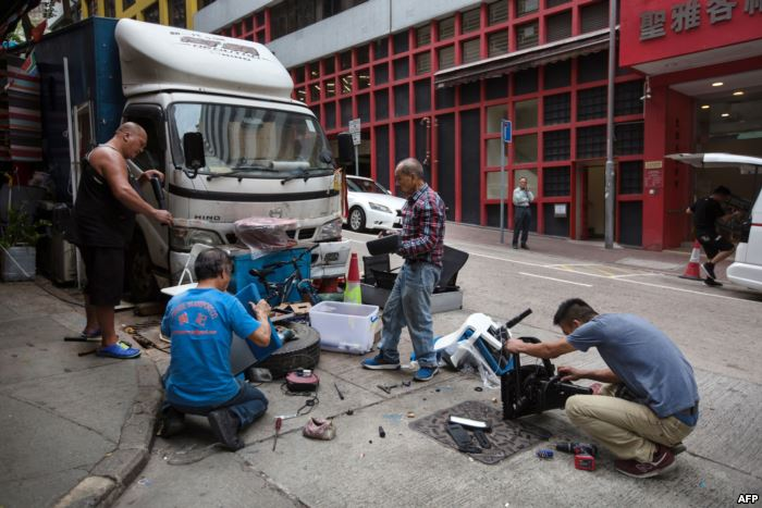 A man watches as people salvage usable materials from discarded office furnit