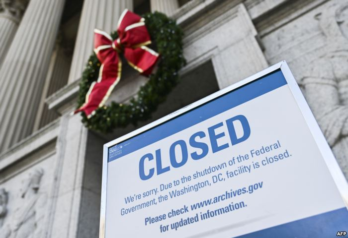 A sign is displayed at the National Archives building that is closed because