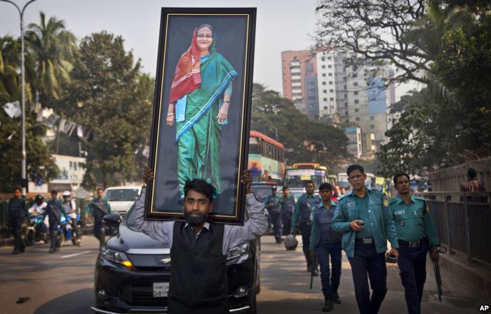 A supporter of Bangladesh Awami League party carries a huge photograph of Ban