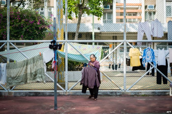 An elderly woman collects items of laundry that were hung out to dry along fe