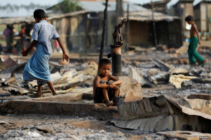 FILE - A boy sits in a burned area after fire destroyed shelters at a camp fo