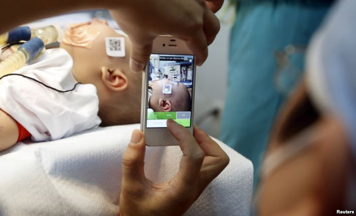 FILE - A doctor uses a smartphone to take a photo of a child with facial defo
