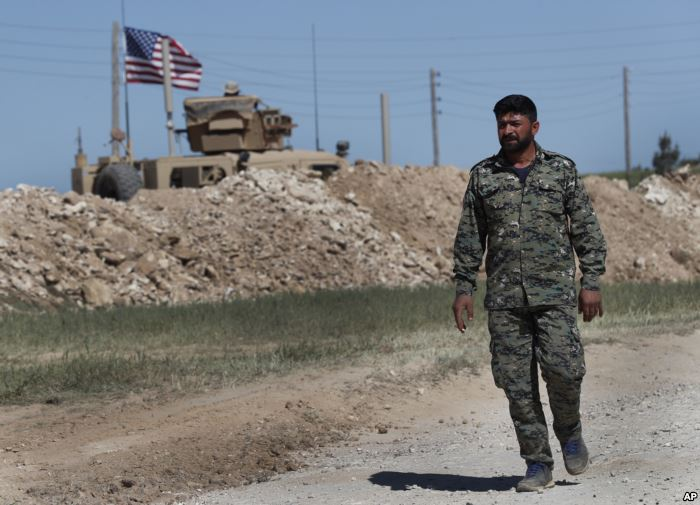 FILE - A U.S-backed Syrian Manbij Military Council soldier passes a U.S. posi