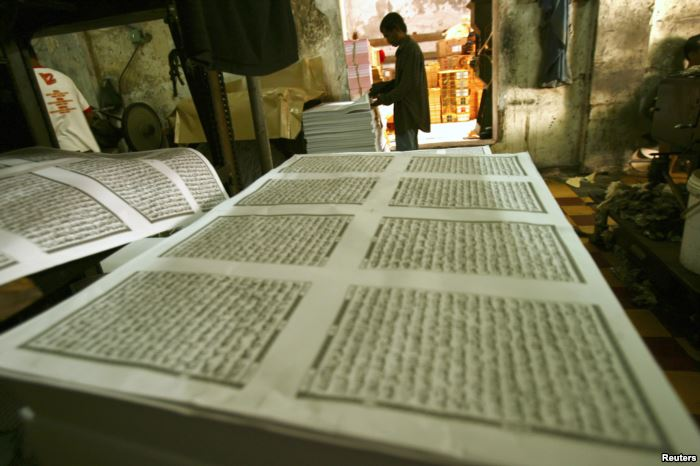 FILE - A worker looks checks printing paper for the Koran near the Sunan Ampe