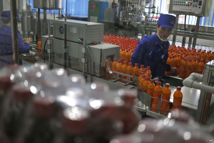 FILE - A worker monitors the production of bottled beverage at Songdowon Gene