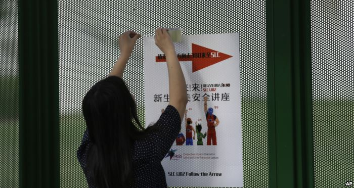 FILE - Ailu Xu, a graduate student from China, posts a sign directing Chinese