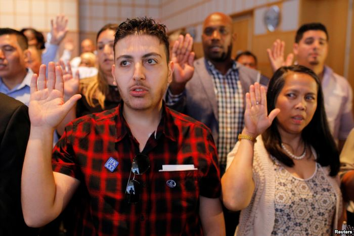 FILE - Applicants take the oath to become new U.S. citizens during a ceremony
