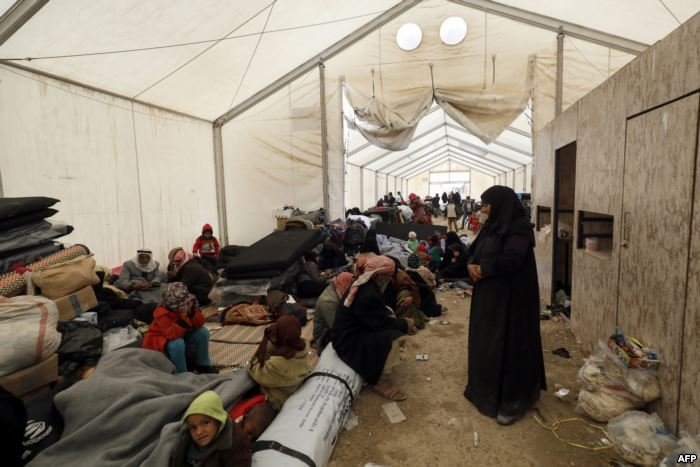 FILE - Displaced people gather inside a tent in the al-Hol camp in northeaste