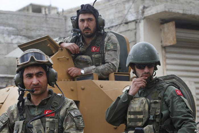 FILE - In this March 24, 2018 file photo, Turkish soldiers atop an armored pe