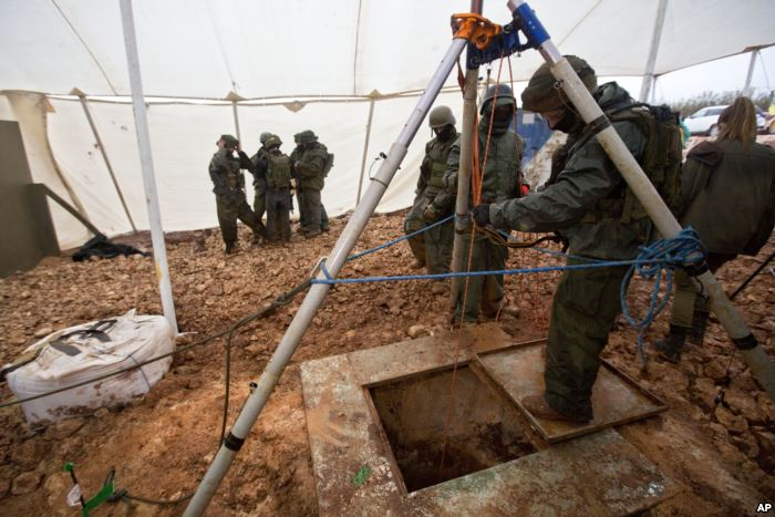 FILE - Israeli soldiers stand around the opening of a hole that leads to a tu