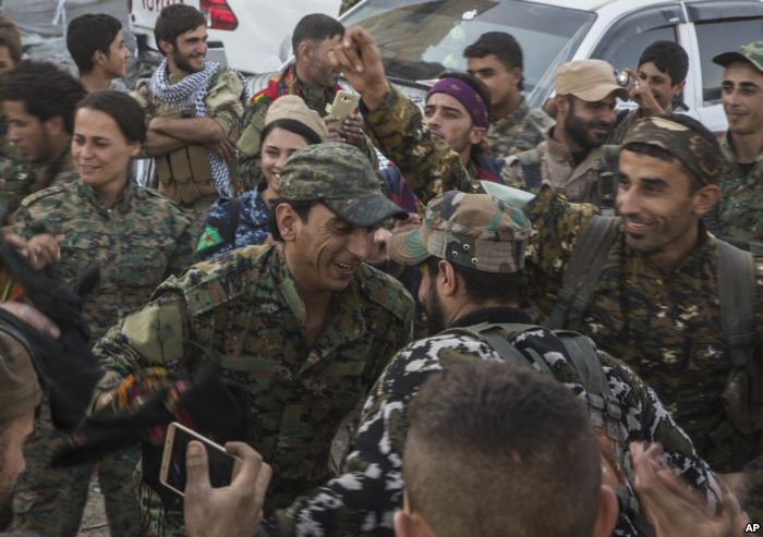 FILE - Members of the U.S.-backed Syrian Democratic Forces (SDF) dance a trad