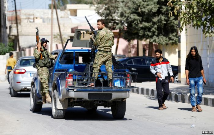 FILE - Members of Turkish-backed Free Syrian Army (FSA) patrol in the border